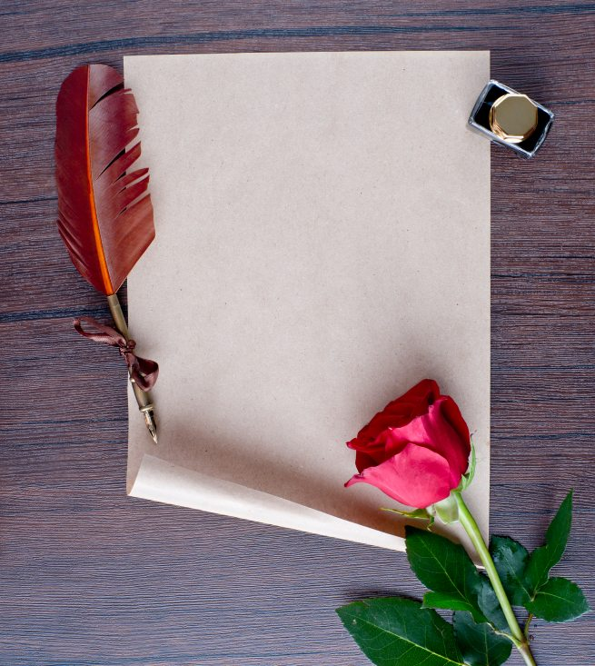 pen and old paper with a rose on a wooden table